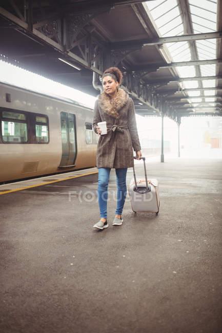 Femme portant des bagages tout en marchant sur le quai de la gare — Photo de stock