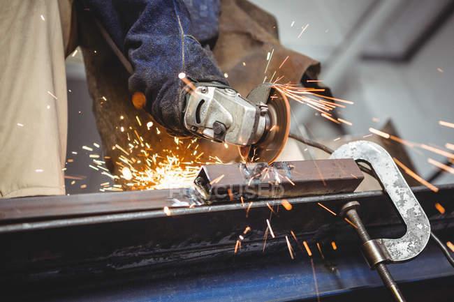Обрезанное изображение сварочного режущего металла с электрическим инструментом в мастерской — стоковое фото