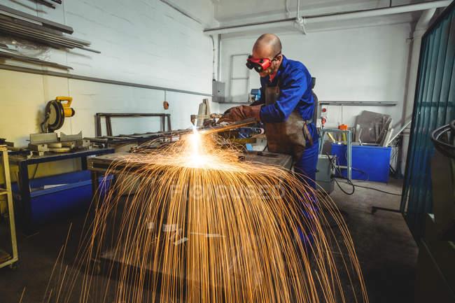 Soldador masculino trabalhando em peça de metal na oficina — Fotografia de Stock