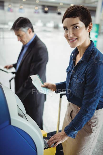 Femme d'affaires à l'aide de self service machine d'enregistrement automatique à l'aéroport — Photo de stock