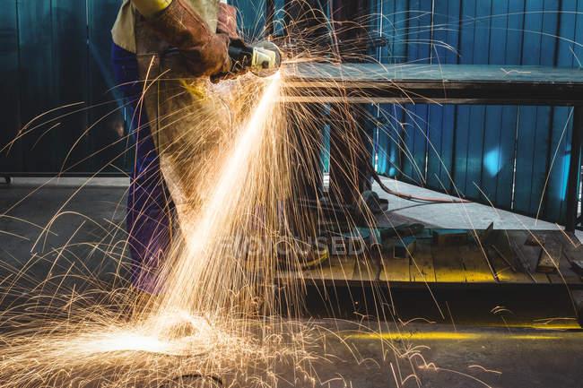 Обрезанное изображение Мужского сварочного аппарата, работающего на куске металла в мастерской — стоковое фото