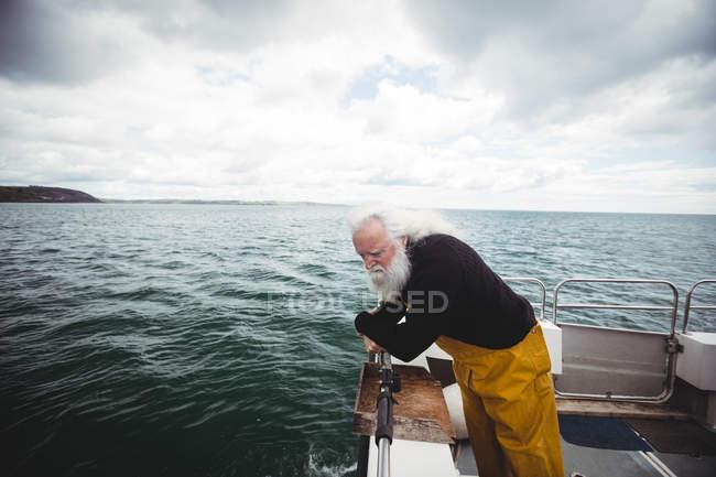 Senior Fischer Blick ins Meer von Fischerboot — Stockfoto