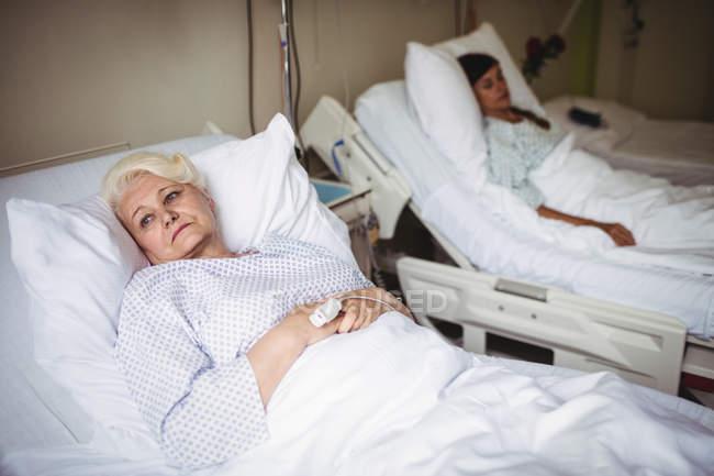 Mujer mayor reflexiva en una cama en el hospital - foto de stock