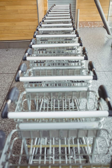 Trolleys kept in a row in airport terminal — Stock Photo