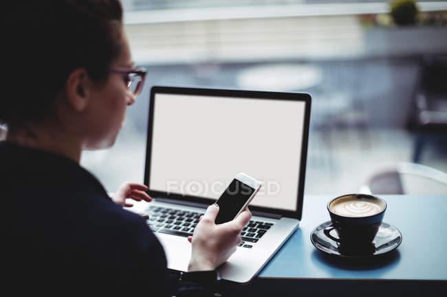 Woman with laptop using mobile phone at table in cafe — Stock Photo