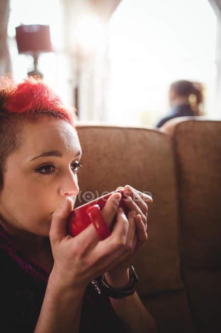 Junge Hipster Frau trinkt Kaffee sitzend auf Sofa zu Hause — Stockfoto