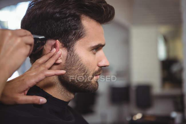 Parrucchiere che taglia capelli di cliente a salone di capelli — Foto stock