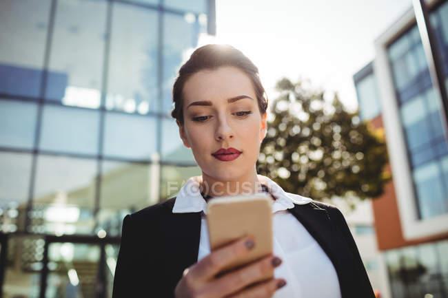 Junge Geschäftsfrau fährt mit Handy gegen Gebäude — Stockfoto