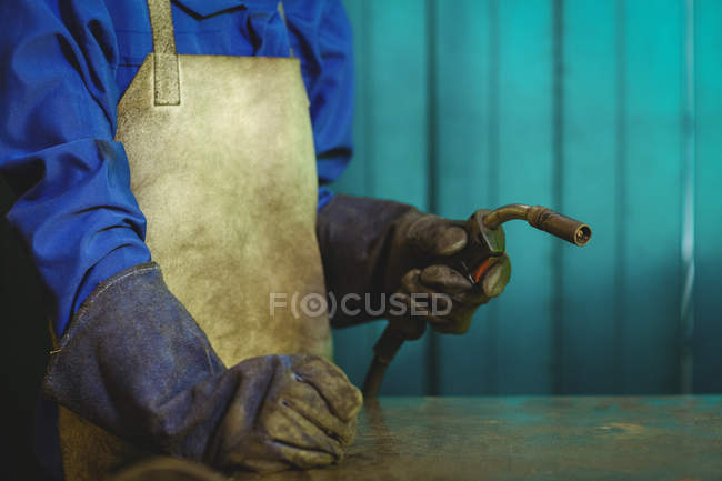 Midsection of female welder holding welding torch in workshop — Stock Photo