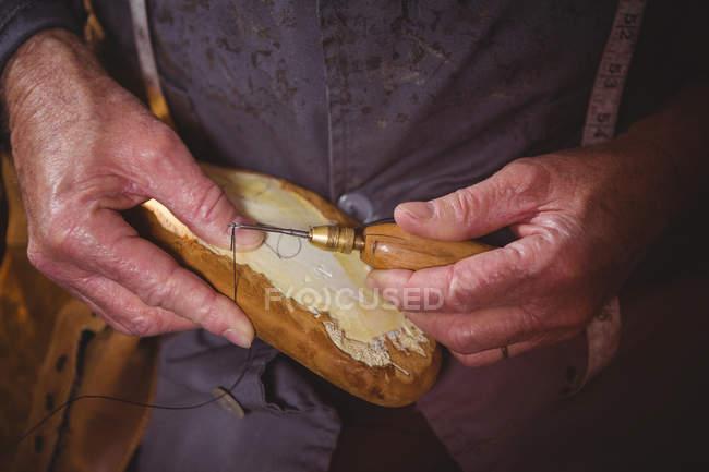 Mãos de sapateiro costura sapato único com agulha na oficina — Fotografia de Stock