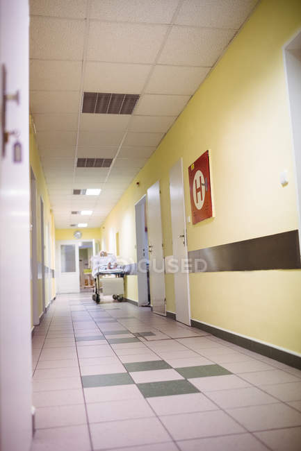 Interior view of corridor in hospital with female patient in background — Stock Photo