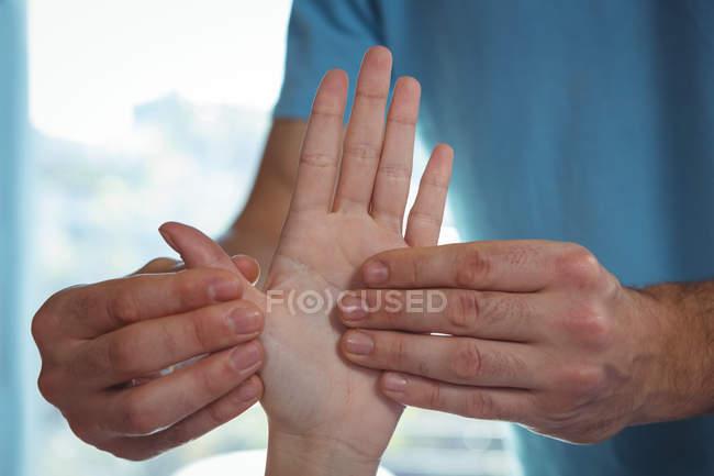 Geschnittenes Bild eines männlichen Physiotherapeuten, der einer Patientin in der Klinik die Hand massiert — Stockfoto