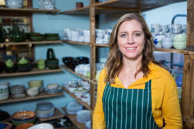 Happy female potter standing in pottery workshop — Stock Photo