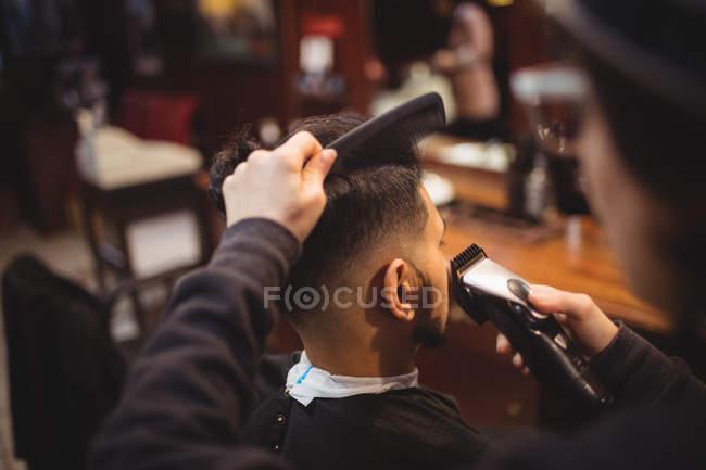 Человек, получать его волосы, подстриженные триммер в парикмахерской — стоковое фото