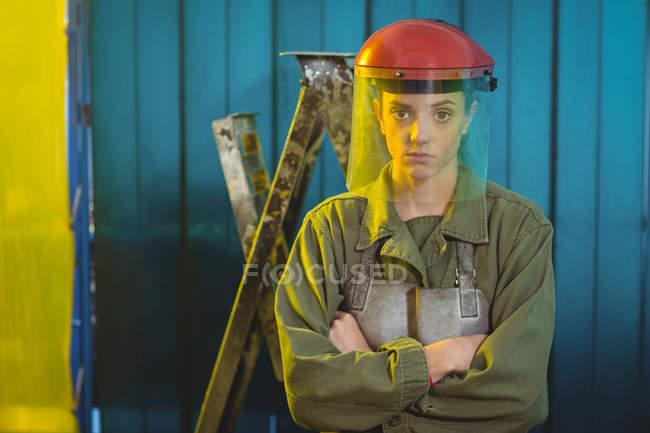 Porträt einer Schweißerin, die mit verschränkten Armen in der Werkstatt steht — Stockfoto