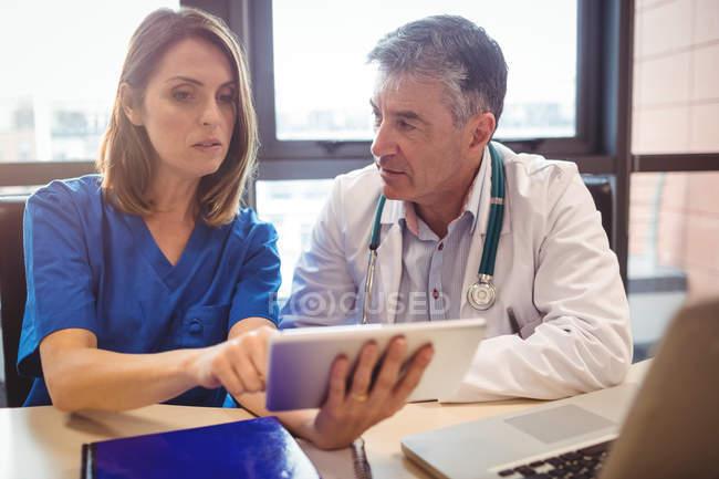 Arzt diskutiert mit Krankenschwester über digitales Tablet im Krankenhaus — Stockfoto