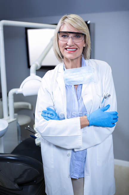 Portrait of confident dentist standing with arms crossed at dental clinic — Stock Photo
