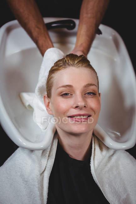 Seque el cabello de la mujer con la toalla en el salón de peluquería - foto de stock