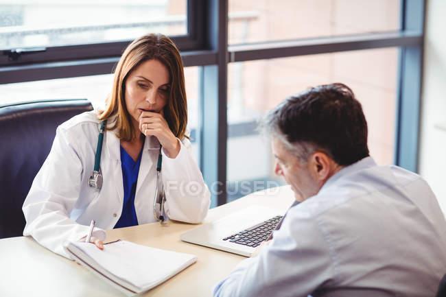 Médica mulher na mesa conversando com paciente no hospital — Fotografia de Stock