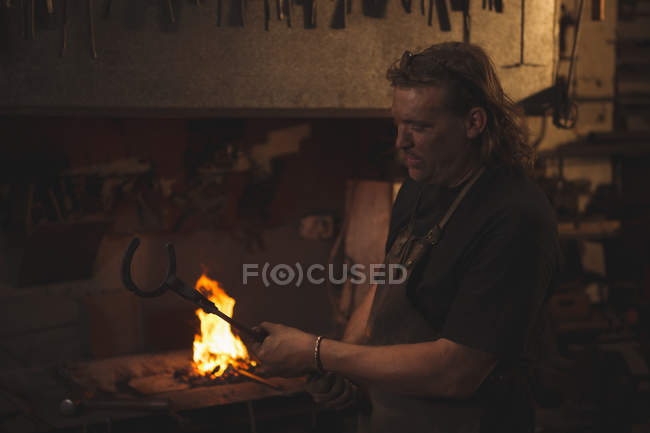 Blacksmith holding metal horseshoe with tongs at work shop — Stock Photo