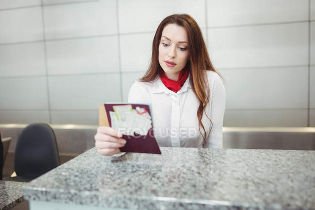 Airline check-in attendant checking passport at check-in counter in airport — Stock Photo