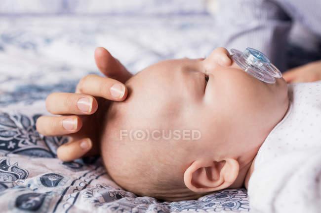 Primo piano del bambino che dorme con manichino in bocca sul letto a casa — Foto stock