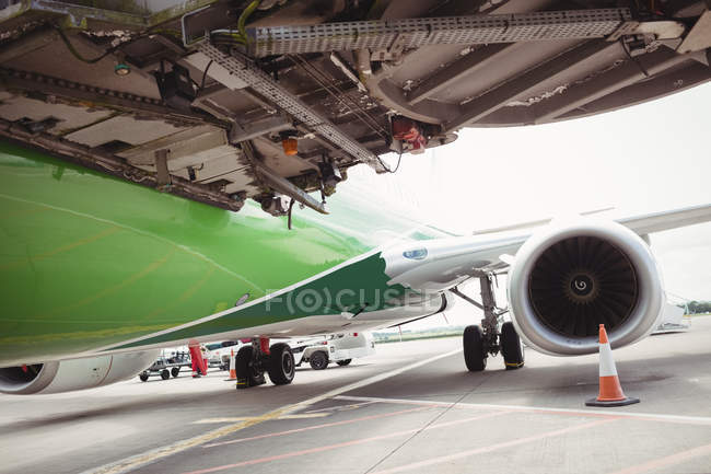 Airplane with loading bridge getting ready for departure at airport terminal — Stock Photo