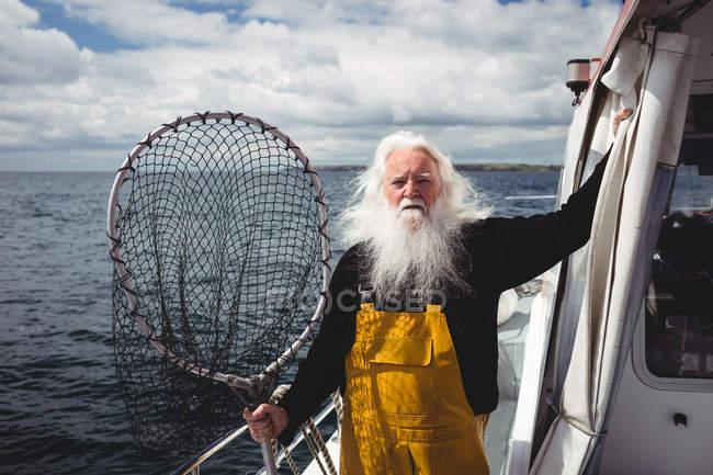Porträt eines Fischers mit Fischernetz auf dem Boot — Stockfoto