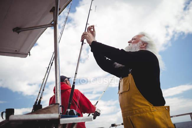 Niedrigwinkel-Ansicht des Fischers Vorbereitung Angelrute auf Fischerboot — Stockfoto