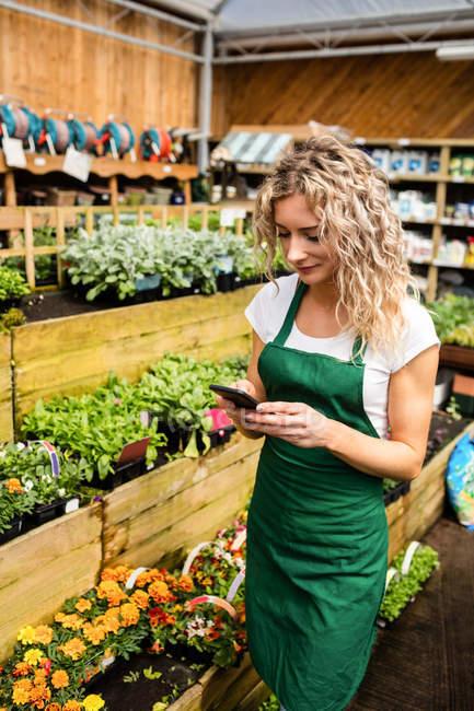 Female florist using mobile phone in garden centre — Stock Photo