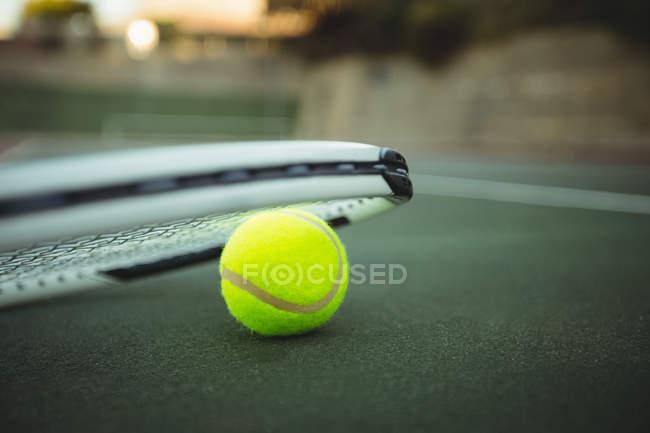 Primer plano de la raqueta de tenis y la bola en la corte verde - foto de stock