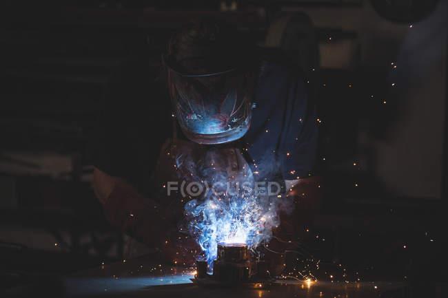 Blacksmith welding a piece of metal in workshop — Stock Photo