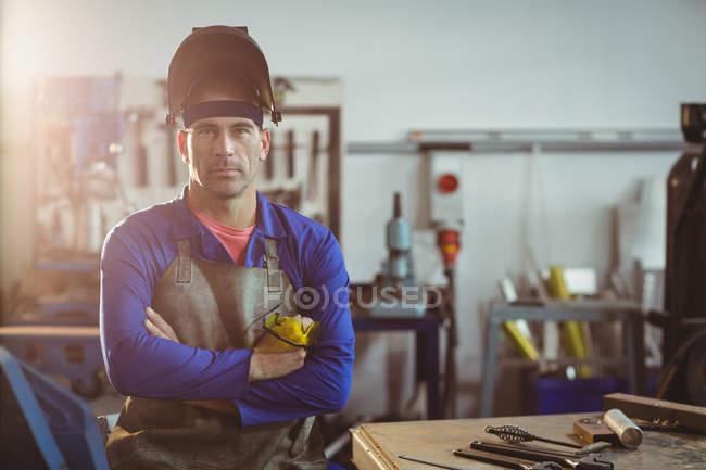 Porträt eines Schweißers, der mit verschränkten Armen in der Werkstatt steht — Stockfoto