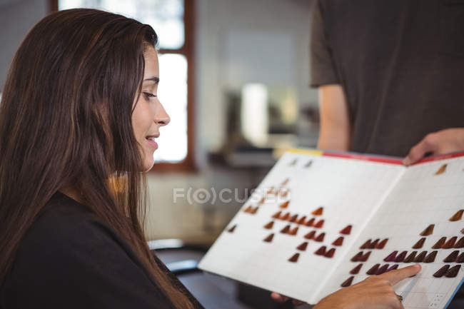 Smiling woman selecting hair color with stylist at hair salon — Stock Photo