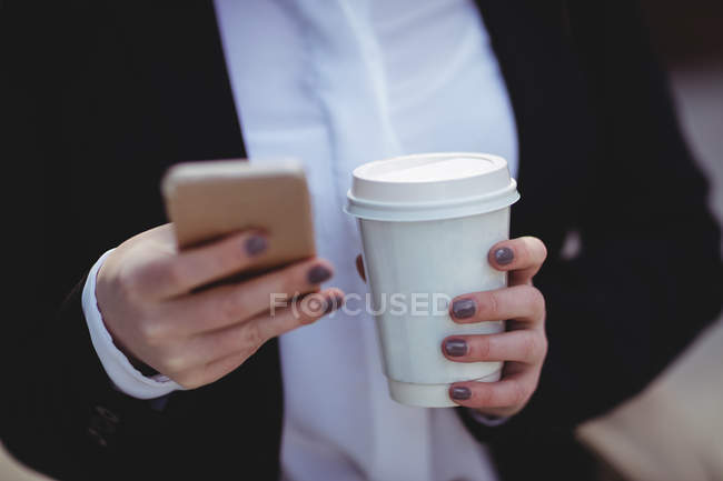 Midsection of woman holding mobile phone and disposable coffee cup — Stock Photo