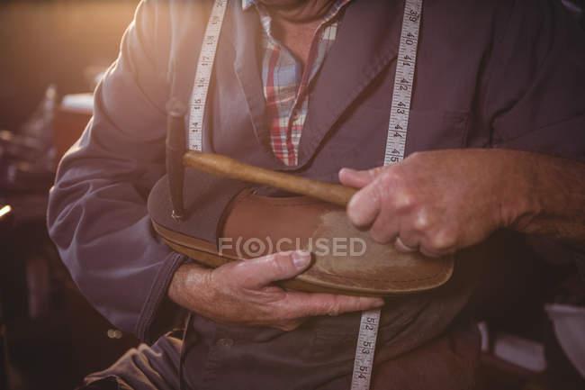 Seção média de sapateiro martelando em um sapato na oficina — Fotografia de Stock