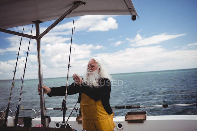 Gris de pelo pescador ajuste anzuelo en barco de pesca - foto de stock