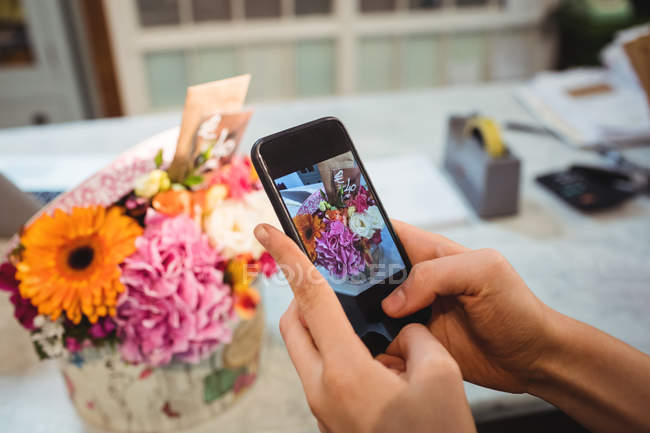 Hands of female florist taking photograph of flowers in the flower shop — Stock Photo