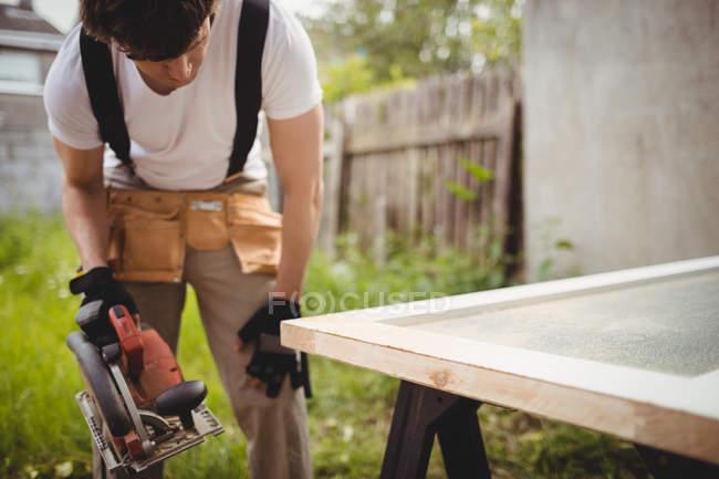 Плотник работает с циркулярной пилой снаружи дома — стоковое фото