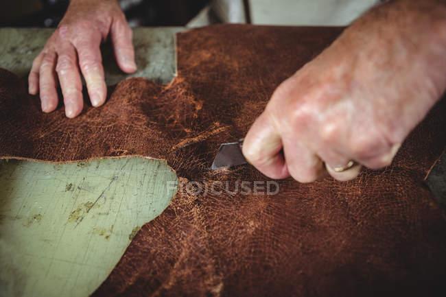 Руки шевця різання шматок шкіри в майстерні — стокове фото