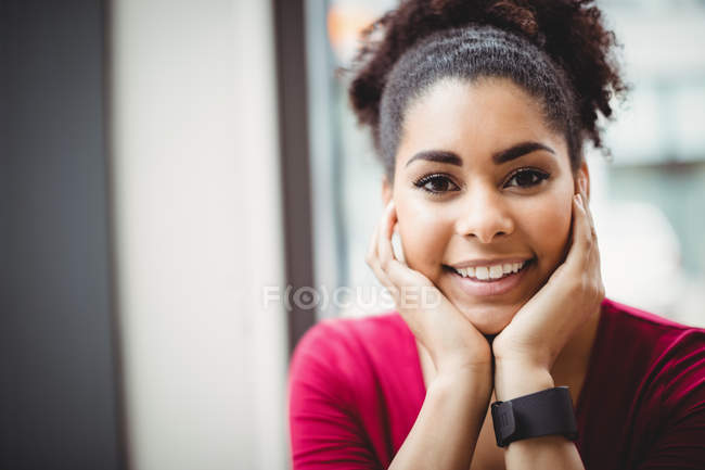 Portrait of cheerful woman with hand on chin at restaurant — Stock Photo