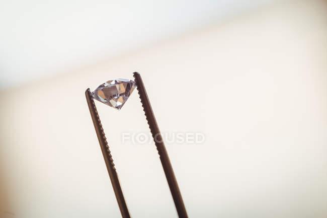 Крупный план алмаза в щипцах в мастерской — стоковое фото