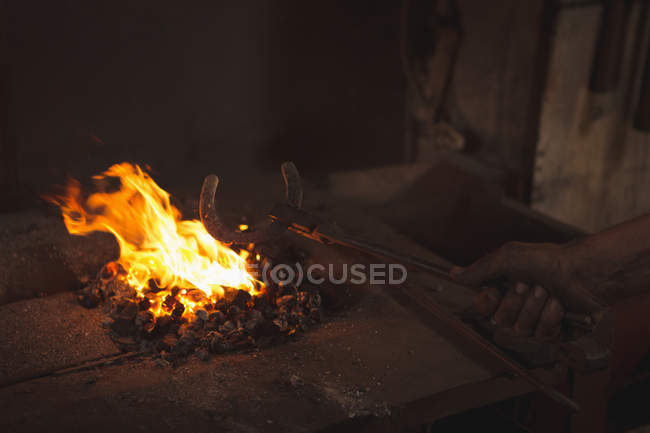 Hand of blacksmith heating a piece of metal in workshop — Stock Photo