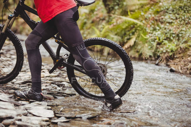 Low section of mountain biker crossing stream in forest — Stock Photo