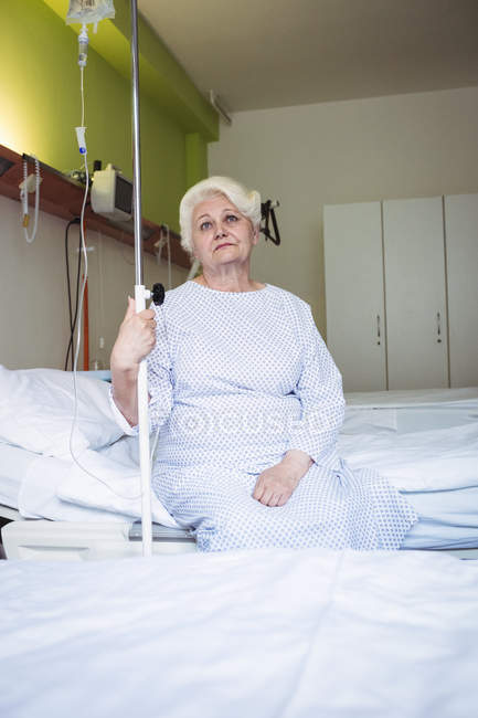 Thoughtful senior woman sitting on bed in hospital — Stock Photo