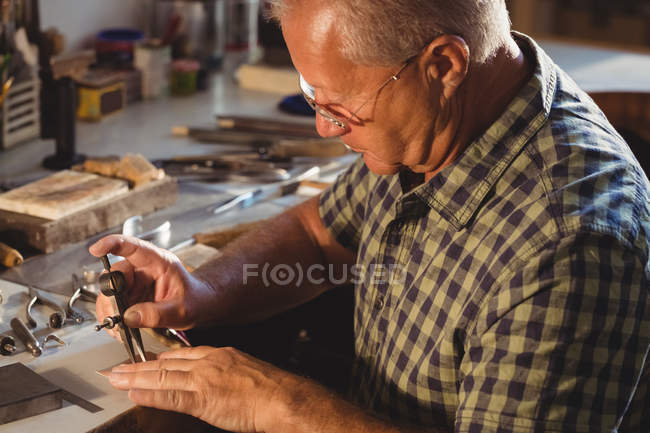 Goldsmith working with divider compass in workshop — Stock Photo