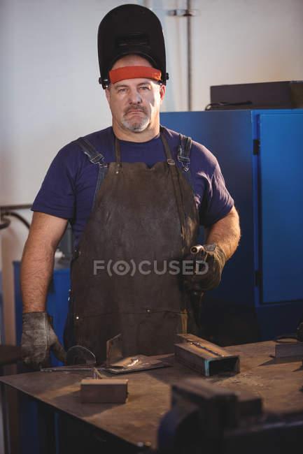 Portrait of welder standing with welding machine in workshop — Stock Photo