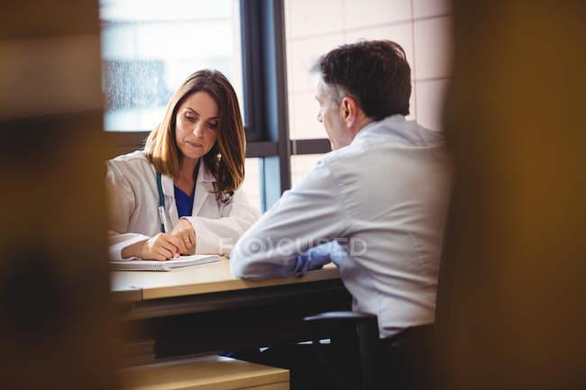 Женщина-врач сидит за столом, пишет в блокноте перед пациентом в больнице — стоковое фото