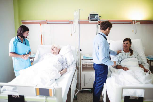 Врачи, взаимодействующие с пациентами в стационаре — стоковое фото