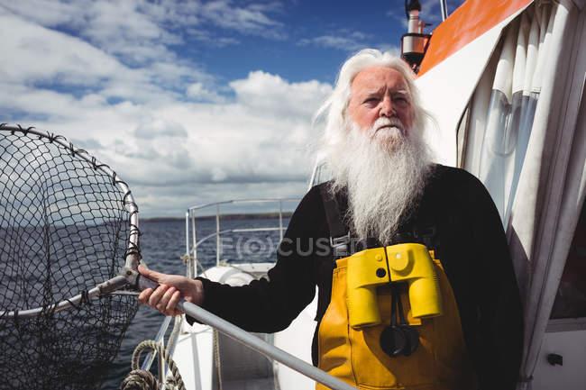 Fischer hält Fischernetz auf Boot — Stockfoto